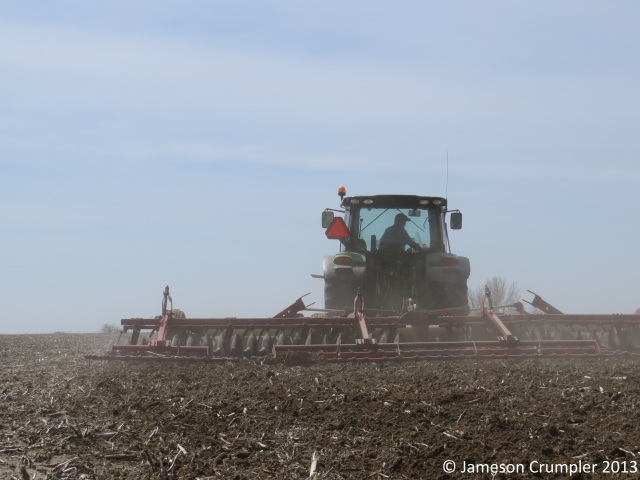 The site is being disc plowed to break up the corn rows and corn stubble prior to restoration planting.